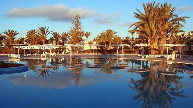 El Mouradi Djerba Menzel Hauptpool im Morgenrot mit Wasserspiegelung
